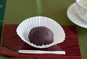 A sesame-seed ohagi cut in half so you can see the anko